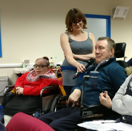 Daphne Branchflower, seated in wheelchair wearing red jumper. Ellen Clifford holding Microphone. Mark Williams speaking into microphone.
